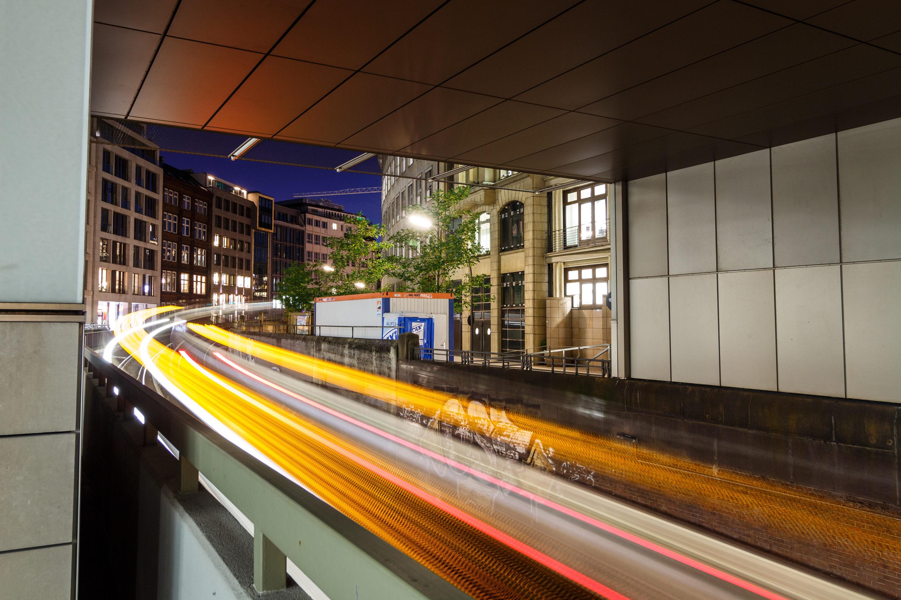 Zwei Nahverkehrszüge, die in der Nacht auf ein Viadukt herauffahren