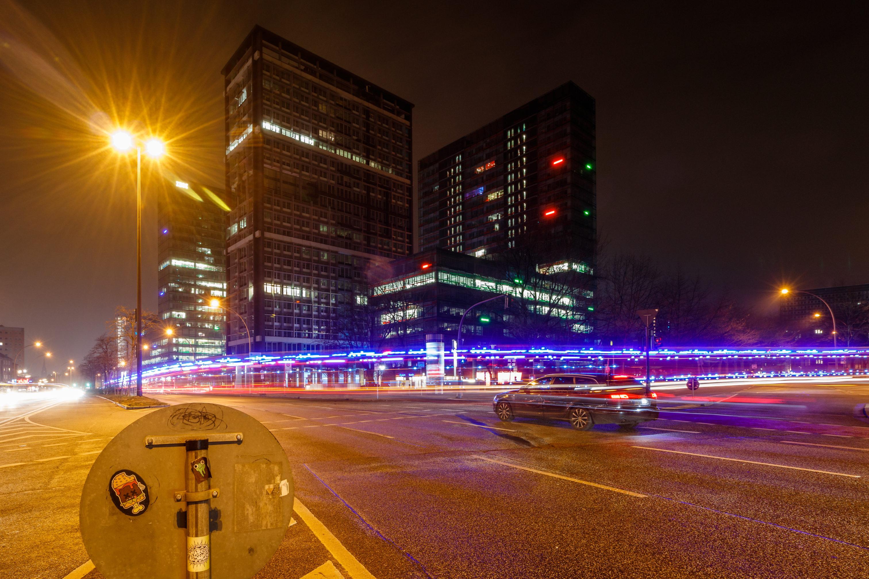 Eine Kreuzung in einer Stadt; von rechts sieht man eine Spur mit Blaulicht in das Bild kommen