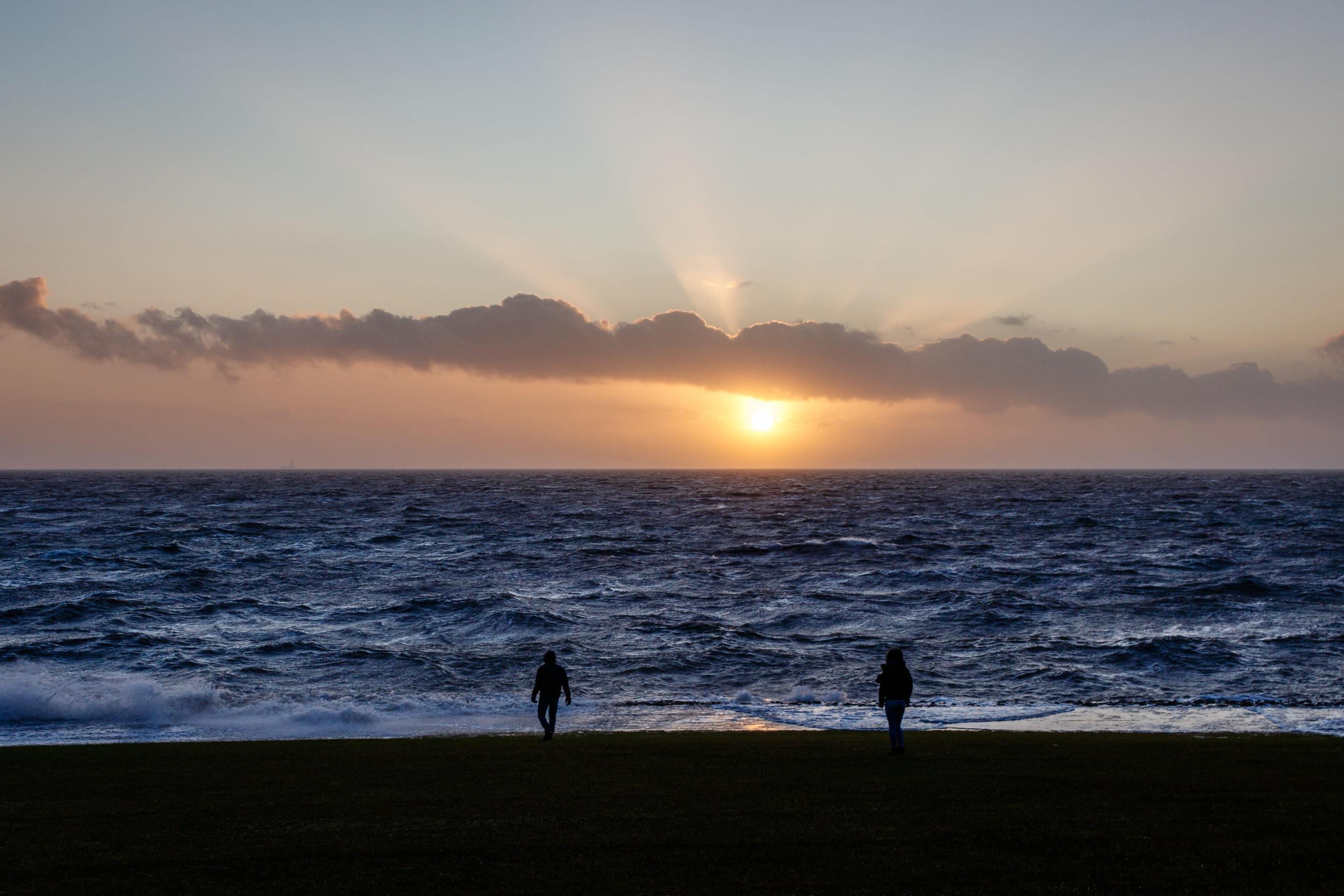 Zwei Menschen vor der untergehenden Sonne am Meer