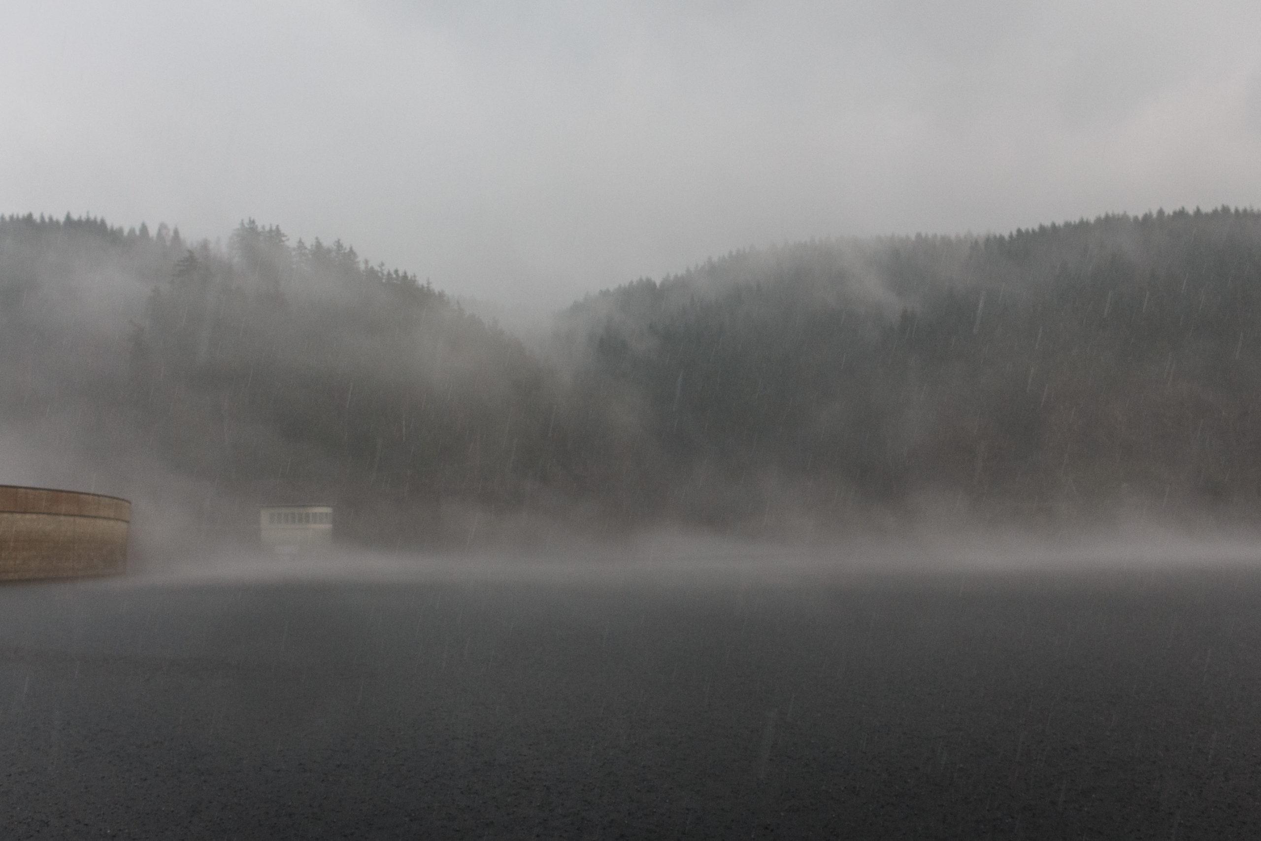 Talsperre im Nebel und der Regen ist als Streifen zu sehen