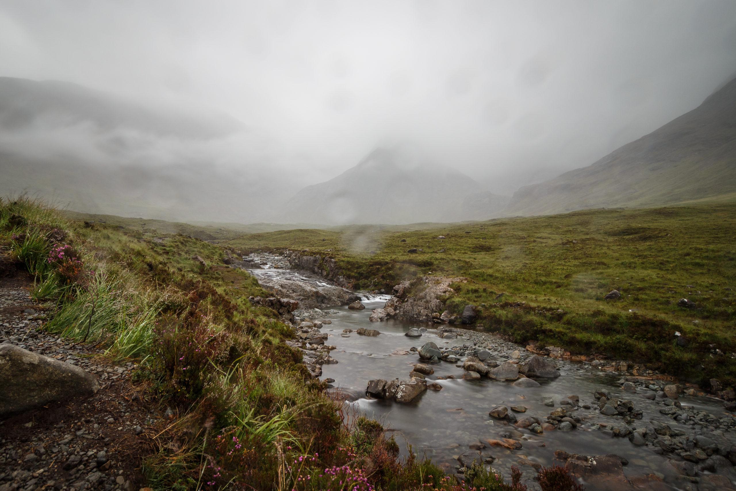 Ein Bach in einer nebelverhangenen Berglandschaft. Im gesamten Bild sind Regentropfen zusehen.