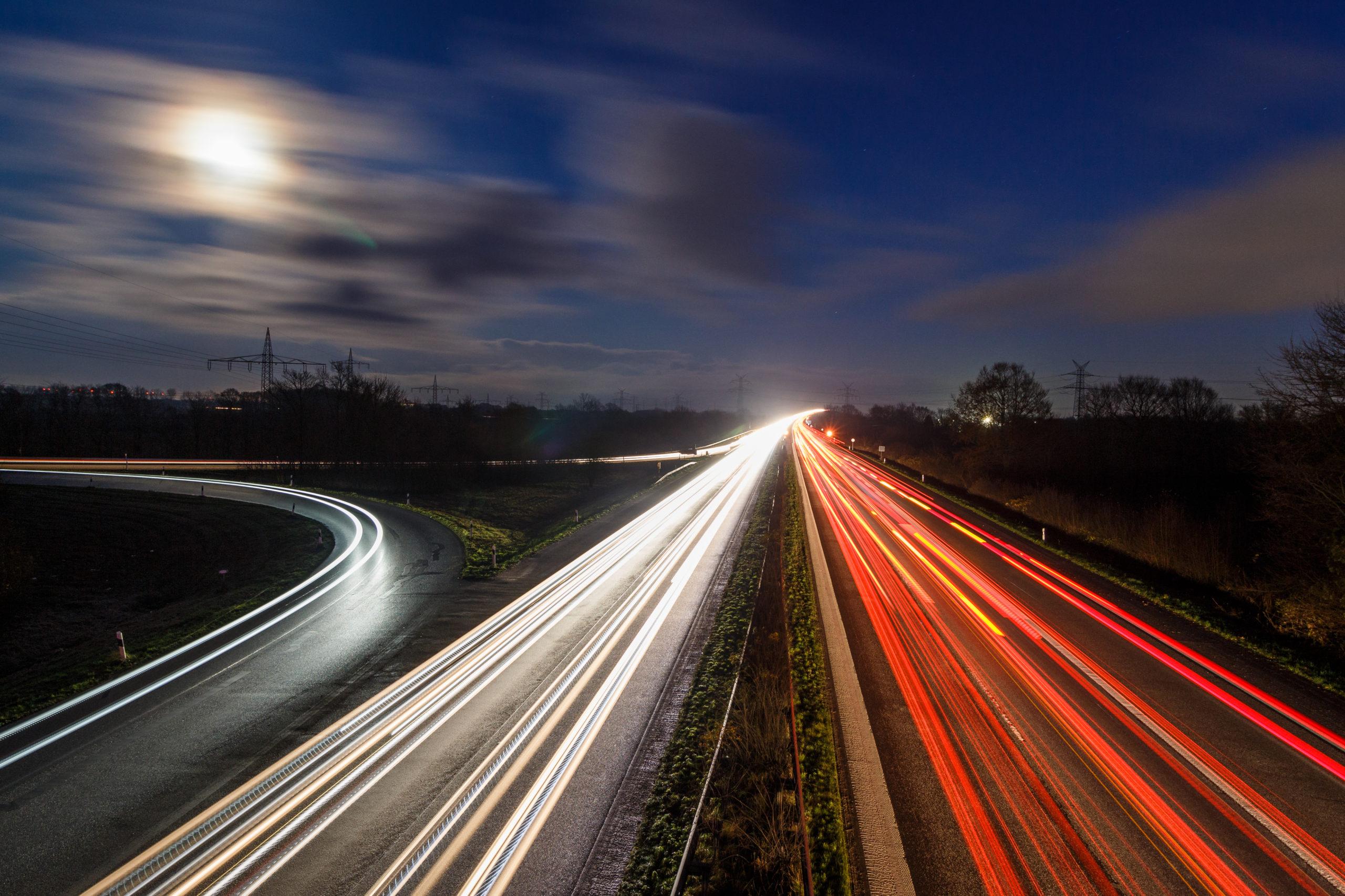 Eine Auto bei Nacht von einer Brücke aus gesehen