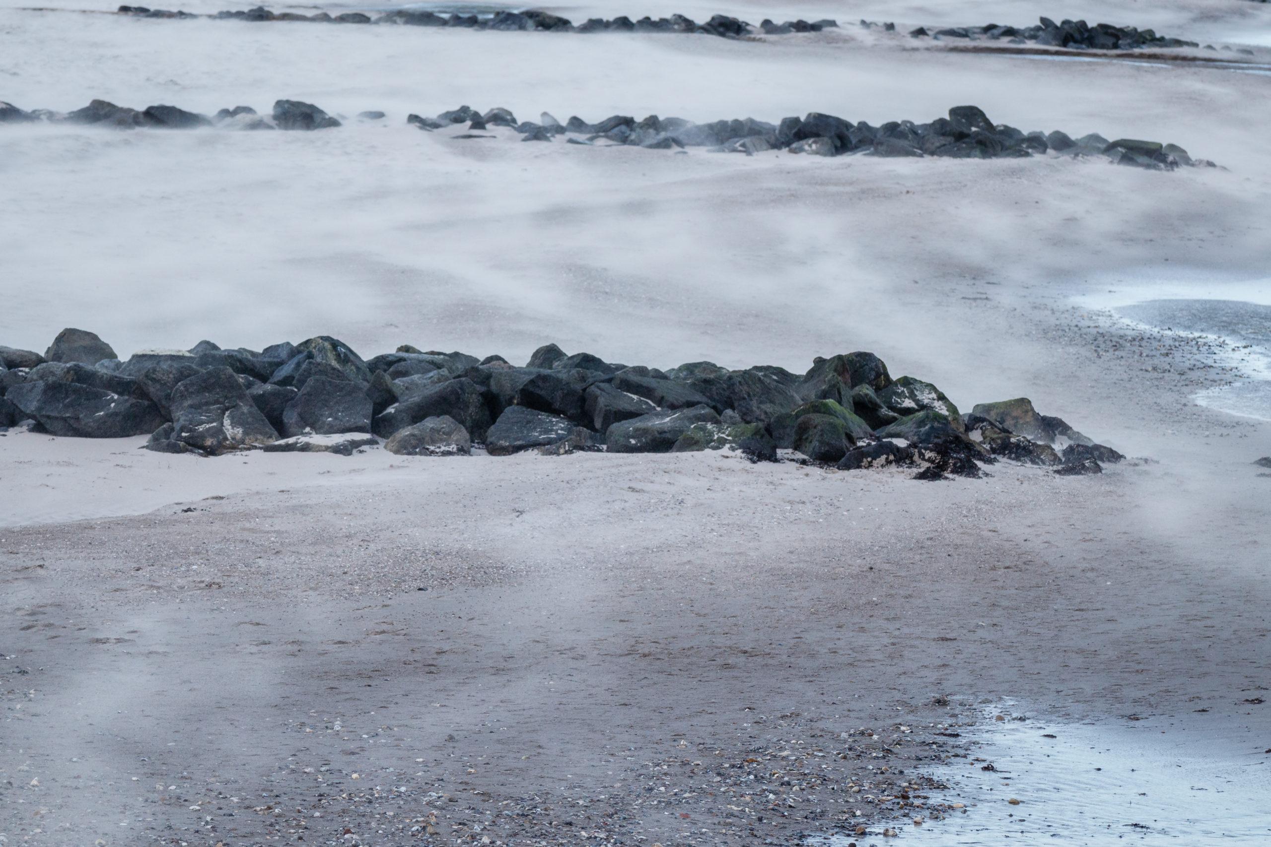 Sand wird vom Wind über den Strand getragen